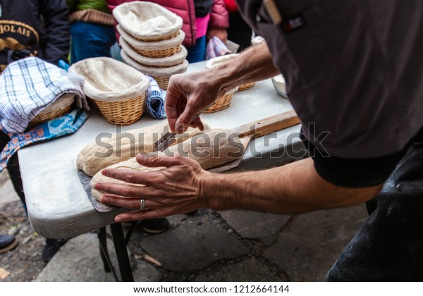 Man is scoring the bread by sliting it with a razor blade before putting it into an outdoor bread oven - Pictures taken during a bread and pizza making workshop