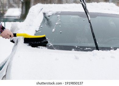 Man scraping snow from hood of car with brush. Person cleaning fresh snow after snowstorm from windscreen car close up.