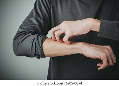 man scratch the itch on his arm