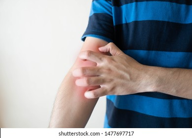 Man scratching arm from having itching  with redness rash over white background. Cause of itchy skin include dermatitis, eczema, psoriasis or fungal infection. Health care concept. Close up.