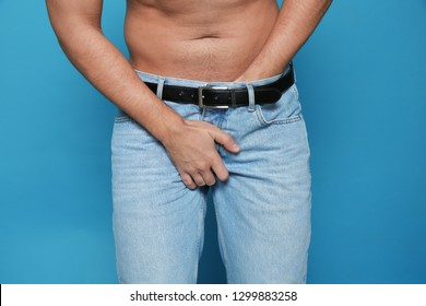 Man scratching crotch on color background, closeup. Annoying itch