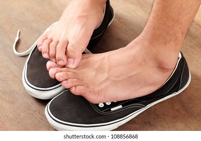 Man scratching his athlete's foot.Close up.