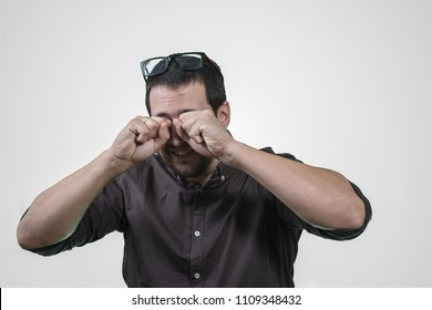 man scratching his eyes with the glasses removed