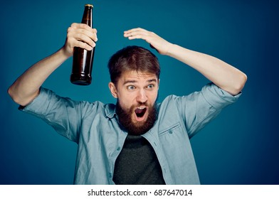 Man screaming and holding a bottle of beer on a blue background.