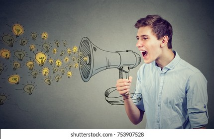 Man screaming out his ideas loud in megaphone isolated on gray wall background