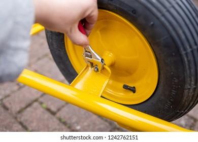 Man screw a wheel of a wheelbarrow