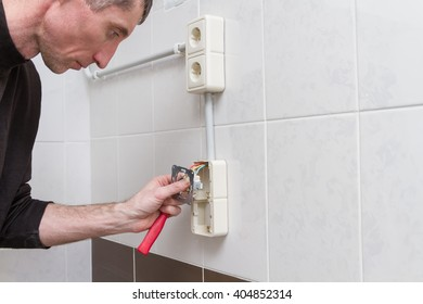 A man with a screwdriver in his hand during the installation of external electrical outlets.