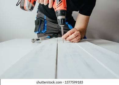A man screwing a screw into a wooden board. The concept of DIY and renovation of new things. A man tinkering at home, working with wood.