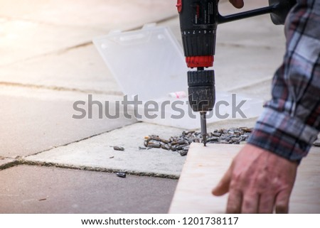 man-screws-piece-wood-using-450w-1201738