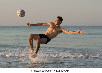 A man in the sea is hitting the ball
