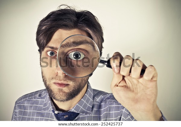 Man seaching through a magnifying lens