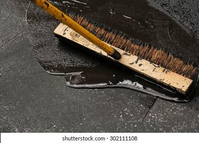 Man sealing asphalt driveway
