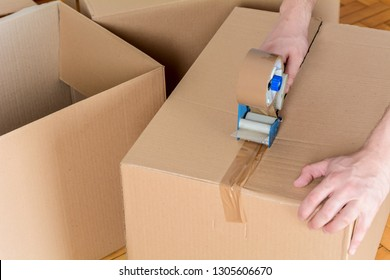 Man sealing a shipping cardboard box with tape dispenser. Indoors
