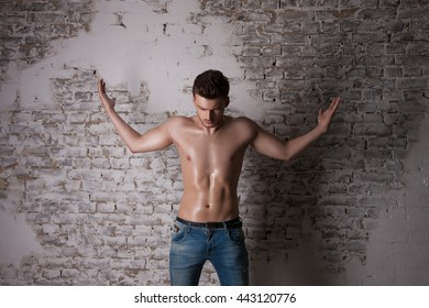 Man in search of answers to questions. Man with a naked torso. Handsome Man with Perfect Body image studio. Pointing hand gesture.