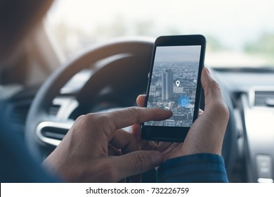 Man searching destination direction or address on gps or navigator application via  mobile smartphone inside a car while driving car, close up