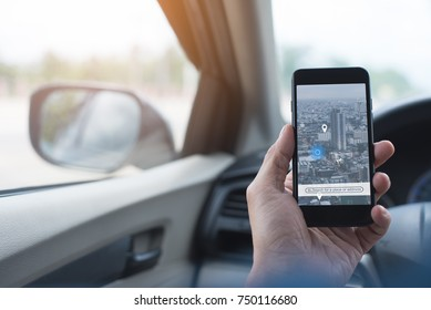 Man searching destination direction or address on gps map or navigator application via  mobile smart phone inside a car while driving car, close up