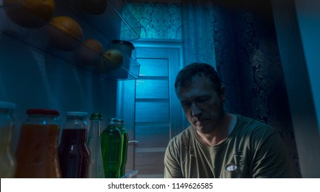 Man searching in his fridge in the darkness for something to snack on during the night viewed from inside standing in the open door