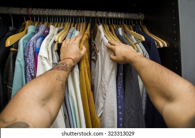 Man searching for a shirt hanging on the rail in his wardrobe, first person point of view looking down his arms. Self POV