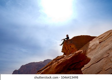 A man seat on the top and look far away, wadi rum, jordan