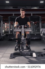 man seated calf raise machine, indoors gym.