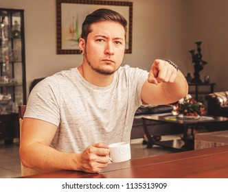 Man seated pointing finger forward with a serious expression like it is showing something or summoning someone. Man seated pointing finger and holding a cup of coffee.