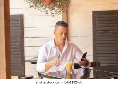 A man seated in a restaurant deliberately looks into the phone and drinks his drink