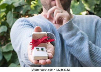 Man with secret surprise holiday christmas gift for a woman with a red bow