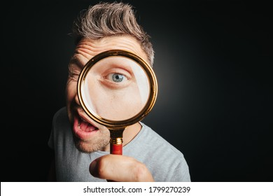 man see through magnifying glass on the black backgrounds. Big man eye - Shutterstock ID 1799270239
