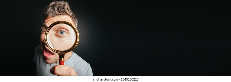 man see through magnifying glass on the black backgrounds. Big man eye - Shutterstock ID 1843150225