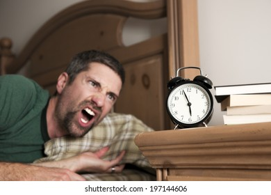 A man seems shocked while noticing the time on an alarm clock.