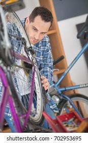 man seller in uniform fixing bike wheel in sport