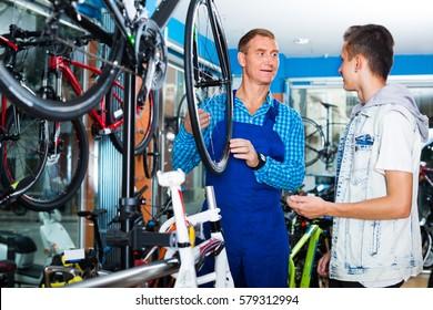 man seller in uniform talking to customer while fixing bike wheel in sport hypermarket