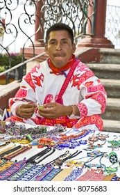a man is selling his jewelry in a flea market