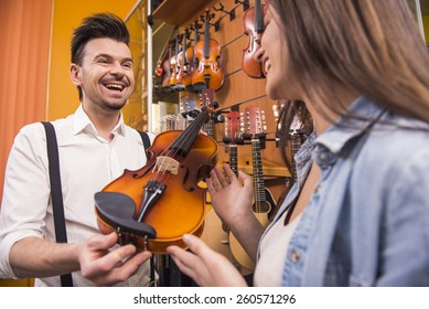 Man is selling violin young girl in a music store.