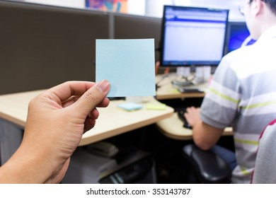 Man sending blue sticky note to colleague who are working at his desk, first person view