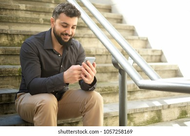 man sending social networking message while smiling