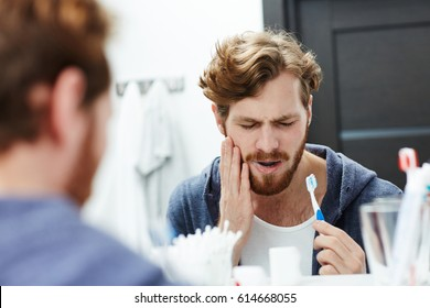 Man with sensitive teeth touching his cheek