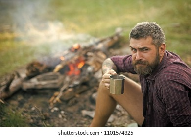 Man with serious emotion. Hipster hiker drink tea at campfire flame. Man traveler with mug relax at bonfire on nature. Camping, hiking, lifestyle. Summer vacation concept. Travel, traveling