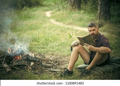Man with serious emotion. Man traveler read and drink at campfire flame. Camping, hiking, lifestyle. Summer vacation, activity. Hipster hiker with book and mug at bonfire in forest. Sustainable
