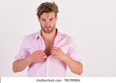 Man with serious face isolated on white background. Macho fastens or unfastens button. Masculinity and style concept. Guy with bristle in pink shirt and messy hair.