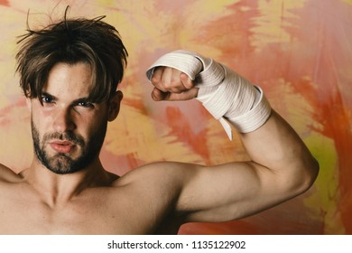 Man with serious face and naked torso on colorful background. Guy with black belt and bandage on arms. Sports and combat concept. Boxer or fighter demonstrates muscles