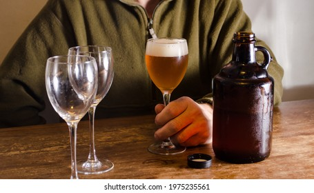 Man serving beer with a growler. Fresh homemade beer in a glass. Drink tasting concept.