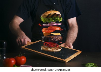 Man serving a delicious layered burger on a serving board