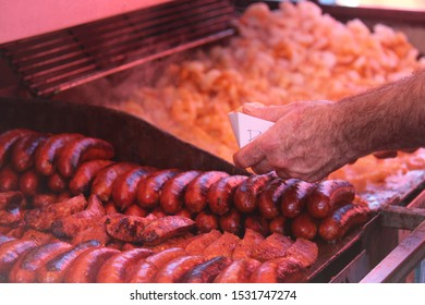 Man serving food from a hot grill with chorizo sausages and prawns at a street fair. Steam is coming off the food as it sizzles