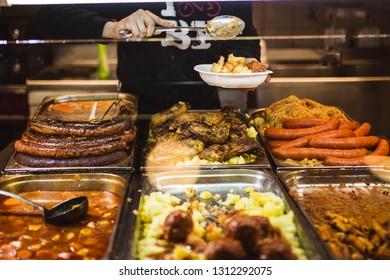 Man serving Hungarian food in a market: potatoes, sausage, sauces