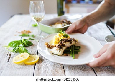 Man serving zander fish fillets on a plate