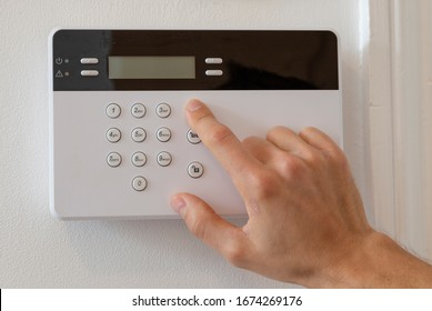 Man setting up an alarm in a flat. Activating the anti burglary alarm. Hand pressing the activation button in a white and black pad