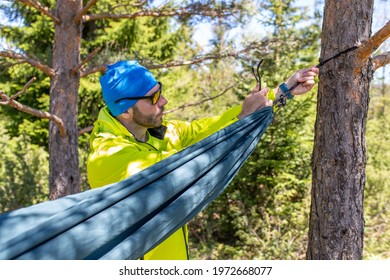 Man is setting up a hammock between two trees in the mountain.