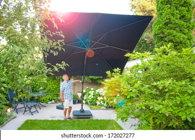 Man setting up a parasol in the backyard on a sunny day