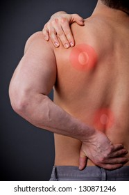 Man with severe back pain holds the shoulder